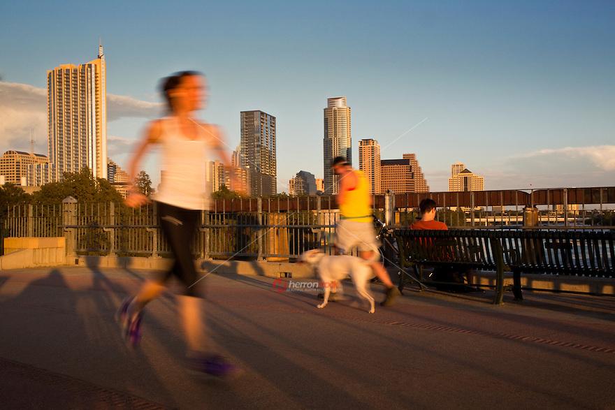 Runners and walkers exercise on the Lamar Street Pedestrian Bridge overlooking the Austin Skyline