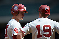 Jordan Vujovich (27) of the Oklahoma Sooners talks to third base coach Clay Van Hook (19) during the game against the Missouri Tigers in game four of the 2020 Shriners Hospitals for Children College Classic at Minute Maid Park on February 29, 2020 in Houston, Texas. The Tigers defeated the Sooners 8-7. (Brian Westerholt/Four Seam Images)