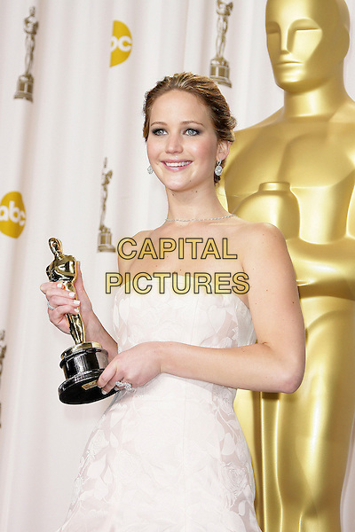 Jennifer Lawrence (wearing Dior Haute Couture) .85th Annual Academy Awards held at the Dolby Theatre at Hollywood & Highland Center, Hollywood, California, USA..February 24th, 2013.pressroom oscars half length white pale pink strapless dress gown voluminous award trophy winner   .CAP/ADM.©AdMedia/Capital Pictures.