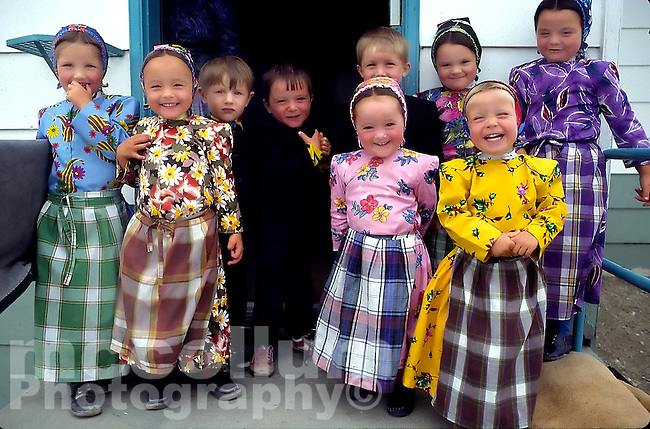 A group of colorfully dressed Hutterite school Children in front of their schoolroom in a colony in Smiley Saskatchewan.