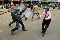 Bangladeshi police baton charge an activist to stop him from marching towards the Pakistani Embassy in Dhaka, Bangladesh.