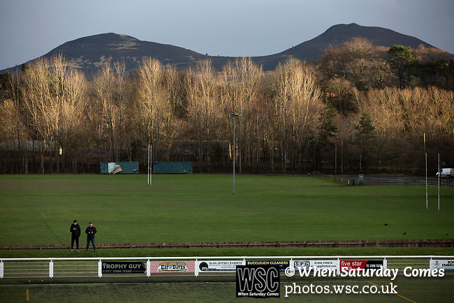 Gala Fairydean Rovers 4, Gretna 1, 25/01/2020. Netherdale, Scottish Lowland League. Two spectators are framed by the Eildon hills in the background as they await kick-off before Gala Fairydean Rovers host Gretna 2008 in a Scottish Lowland League match at Netherdale, Galashiels. The home club were established in 2013 through a merger of Gala Fairydean, one of Scotland's most successful non-League clubs, and local amateur club Gala Rovers. The visitors were a 'phoenix' club set up in the wake of the collapse of the original club, which had competed for a short time in the 2000s before going bankrupt. The home aside won this encounter 4-1 watched by a crowd of 120. Photo by Colin McPherson.