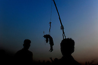 A Bangladeshi Hindu devotee hangs from a rope with hooks pierced in his back as part of a ritual during the Charak Puja festival in Gazipur, near Dhaka, Bangladesh.