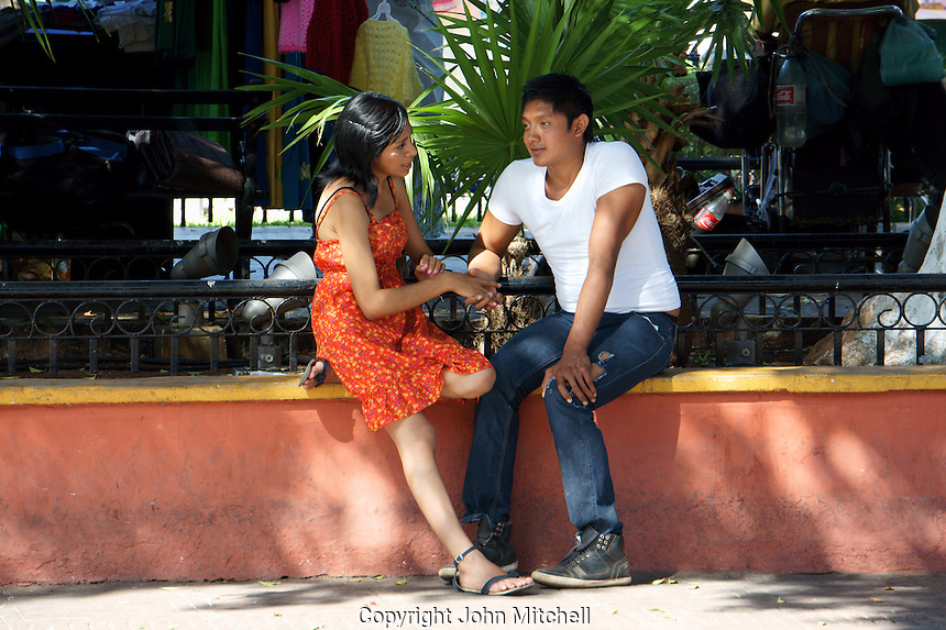 Young lovers sitting on a wall, Plaza Grande, Merida, Yucatan, Mexico.