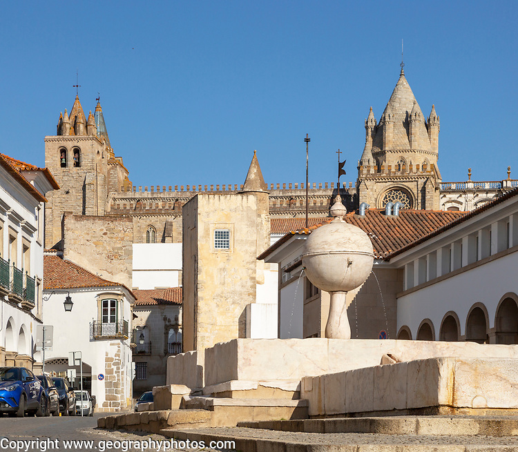 Fountain in the Largo das Portas de Moura with a view to the cathedral and surrounding historic buildings in the city centre of Evora, Alto Alentejo, Portugal, Southern Europe - 23 March 2019