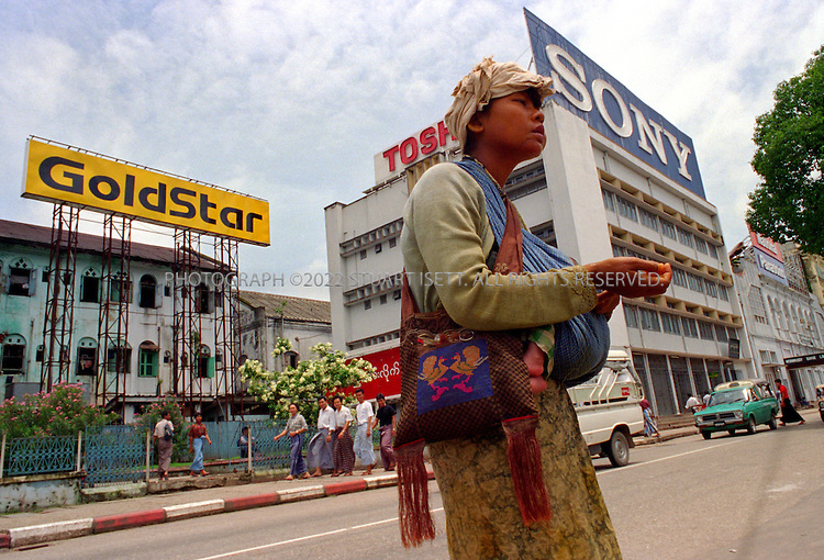7/14/1994--Rangoon, Burma..A beggar on the streets of Rangoon under foreign corporartions' ads as foreign investment pours in Burma...All photographs ©2003 Stuart Isett.All rights reserved.This image may not be reproduced without expressed written permission from Stuart Isett.