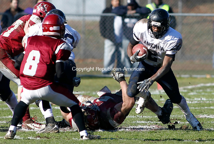 Naugatuck, CT- 24 November 2011-112411CM05-  Ansonia's Arkeel Newsome (2) gains extra yardage as he's tripped up by Naugatuck's Tim Woodfield during their Thanksgiving matchup at Naugatuck High School Thursday morning.  Newsome had 5 touchdowns on the day as Ansonia defeated Naugy 49-14.  Christopher Massa Republican-American