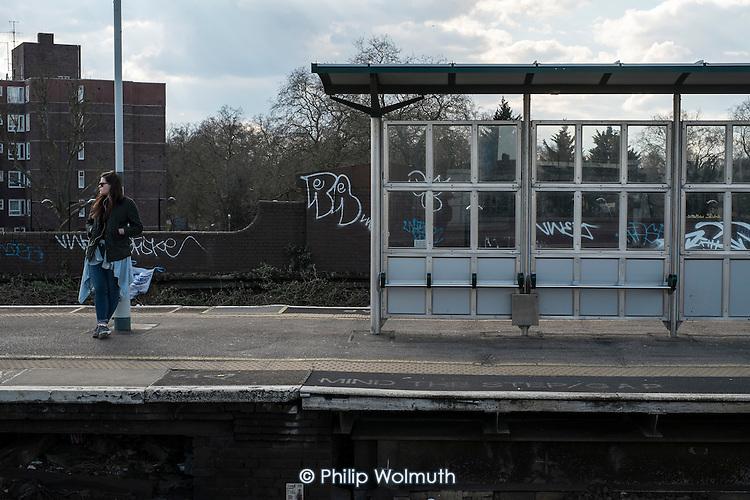 Woman waiting for a train on Battersea Park railway station plaform, London.