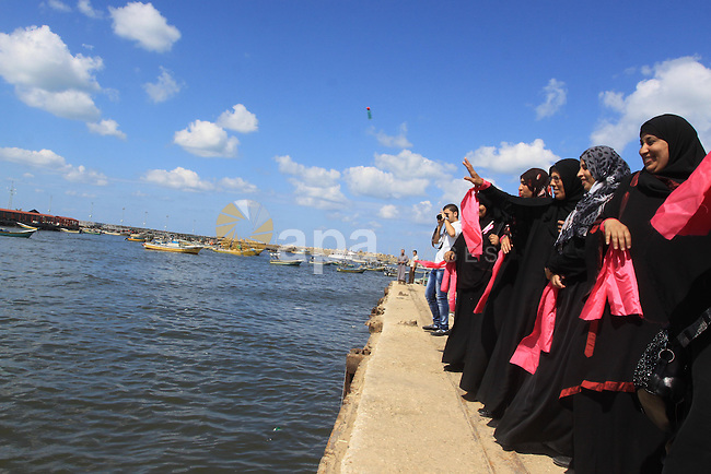 Palestinian women hold banners during the Breast Cancer Awareness campaign at Gaza port in Gaza City on Oct. 01, 2014. Photo by Mohammed Asad