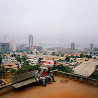 A group of three workers sit on a bench, overlooking Luanda's seafront, during lunch break.