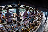 Buddhist Pilgrims lighting oil lamps outside the Sri Maha Bodhi. The sacred bodhi tree. Anuradhapura, North Central, Sri Lanka