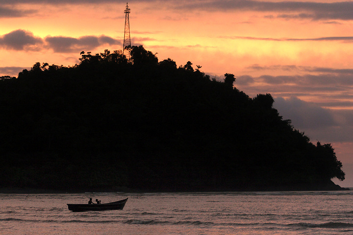 NUQUÍ, EL CHOCO, COLOMBIA -- DECEMBER 12:  Boys fish below a small lighthouse at sunset in Nuqui on December 12, 2005. Nuquí is a small town on Colombia's isolated and untamed Pacific coast, an area sandwiched between endless miles of trackless rainforest and the Pacific Ocean. (Photo by Dennis Drenner/Aurora).