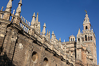 General view of Giralda Minaret and ornate pinnacle topped walls, Seville Cathedral, Andalucia, Spain, pictured on December 27, 2006 in the winter morning light. Seville Cathedral is the largest Gothic building in the world. It was converted from the original 12th century Almohad Mosque on this site during the 16th century and the original Moorish entrance court and Giralda Minaret are both integrated in the cathedral. Inside is the tomb of the explorer Christopher Columbus (1451-1506). The Giralda is constructed of cut bricks, originally 82 metres high, now 103 metres high with the 16th century belfry added to the original tower. Picture by Manuel Cohen