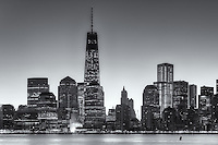 The Freedom Tower (1 World Trade Center) and other buildings of the lower Manhattan skyline are illuminated as the sky brightens shortly before sunrise in New York City.