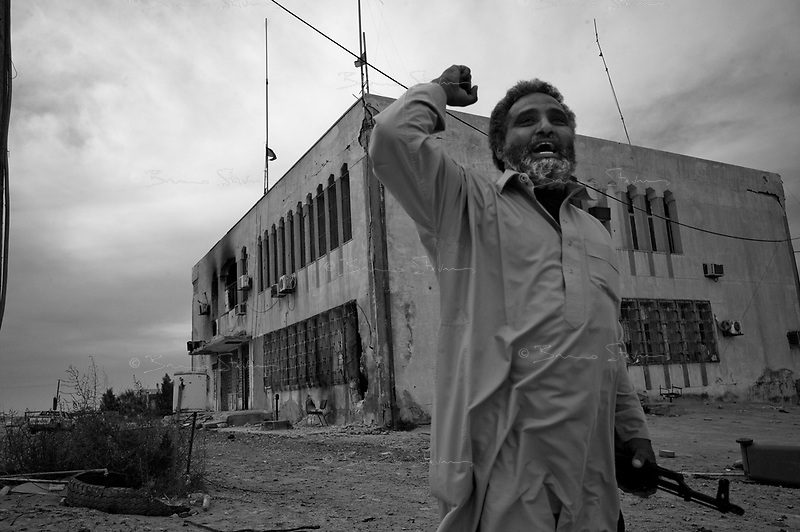 Ben Jawat, Libya, March 12, 2011.Abdel Khader, an local Khaddafi supporter, in front of Ben Jawat  burned down police station. This small town marked the westernmost point reached by rebel forces befor being repelled by Khaddafi's artilery and aviation. Picture taken during an trip for foreign journalists organized by the Libyan Foreign Media department.