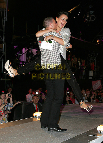 CHARLIE DRUMMOND & DAVINA McCALL.final of Big Brother 10..Elstree Studios, Borehamwood, England. 4th September 2009  .BB10 full length legs kicking funny gesture hug embrace lifting carrying silver black grey gray white check shirt back behind rear sequins sequined mouth open .CAP/ROS.©Steve Ross/Capital Pictures.