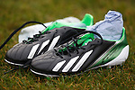 A pair of discarded green and white boots at training