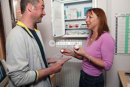 Service Manager giving controlled medication to Service User on detox programme,