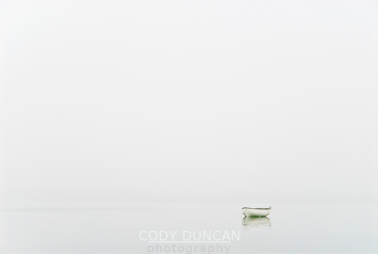 Small row boat in dense fog, Orkney, Scotland