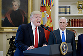 United States President Donald Trump speaks about trade as Vice President Mike Pence looks on before signing Executive Orders  in the Oval Office of the White House March 31, 2017 in Washington, DC. <br /> Credit: Olivier Douliery / Pool via CNP