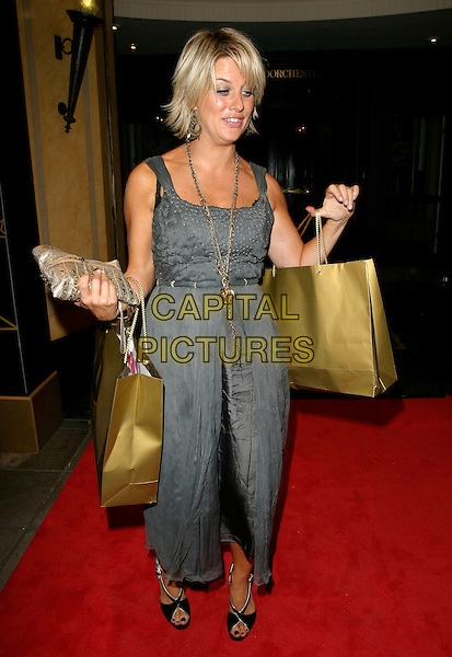 CAROLINE FERRADAY.Leaving the TV Quick & TV Choice Awards 2006,.The Dorchester Hotel, London, England,.September 4th 2006..full length grey dress gold goody bags farraday funny.Ref: AH.www.capitalpictures.com.sales@capitalpictures.com.©Adam Houghton/Capital Pictures.