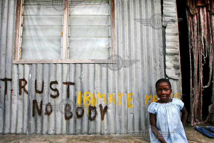 A young girl sits outside her home in Sangana. Graffiti on the zinc-plated house reads: 'Trust No Body'. The locality is oil rich but the community is impoverished and its residents accuse successive Nigerian governments and international oil companies of depriving them of the wealth pumped from their backyards.