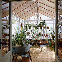 The glass roof of the conservatory has blinds to protect the plethora of pot plants from the full force of the sun