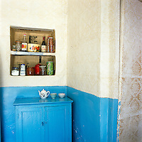 Simple shelving is built into a wall which is part covered with plastic wallpaper and part blue painted concrete