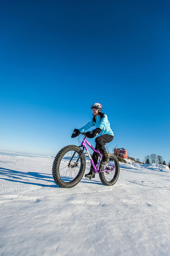 Winter cyclists on fat bikes ride the frozen beach and lake ice of Lake Superior near the Marquette Lighthouse in Marquette, Michigan.