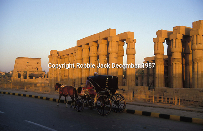 A caleche (carriage) on the Sharia Al-Corniche in front of the Temple at Luxor.The First Pylon of the Temple complex was raised by Ramses II who ruled  Egypt from 1279-1213 BC and the Colonnade was built in the time of Amenhotep III who ruled from 1391-1353 or 1388-1351 BC.The Temple was dedicated to the Theban Triad of  Amun,Mut and Khonsu.The town of Luxor occupies the eastern part of a great city of antiquity which the ancient Egytians called Waset and the Greeks named Thebes.