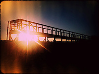 Sunset sunburst through boardwalk on lake. iPhone photo. Manipulated with app.
