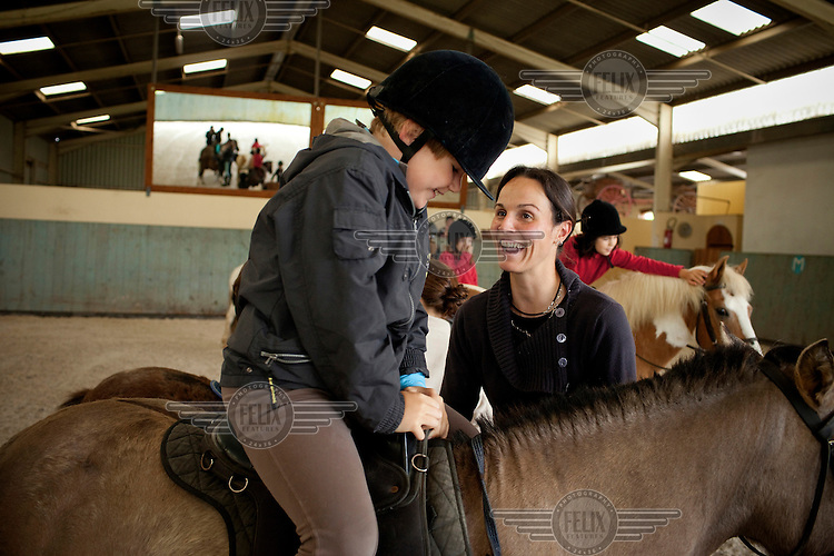 Nathalie Bertranine (centre right) gives a horse riding lesson to a child. To make a living she transformed her parents' traditional farm into a horse-riding centre.