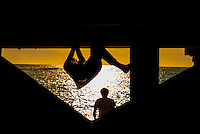 Aberystwyth, West Wales, UK Weather: A young man climbs on the wooden jetty at sunset in Aberystwyth, Wales, UK