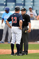 Tampa Yankees manager Al Pedrique (13) talks with umpire Jordan Albarado after a call during a game against the Daytona Cubs on April 13, 2014 at George M. Steinbrenner Field in Tampa, Florida.  Tampa defeated Daytona 7-3.  (Mike Janes/Four Seam Images)