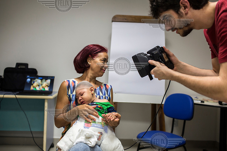 Felipe Rocher Wagner, a graduate student, photographs grandmother, Maria Soares, with her nine-month-old grandson, Pedro Miguel de Lima, for a project, with researchers from the University of Oxford in England, creating three-dimensional photographs to facilitate the study of babies born with Zika-related microcephaly at the Fundacao Altino Ventura. <br /> The foundation provides free therapy classes to families with children born with Zika-related microcephaly. There are 271 confirmed cases at the foundation but due to staffing shortages they can only treat 116 patients.