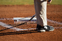 A member of the grounds crew rakes the right side batter's box prior to the Conference USA baseball game between the Rice Owls and the Charlotte 49ers at Hayes Stadium on March 6, 2015 in Charlotte, North Carolina.  The Owls defeated the 49ers 4-2.  (Brian Westerholt/Four Seam Images)