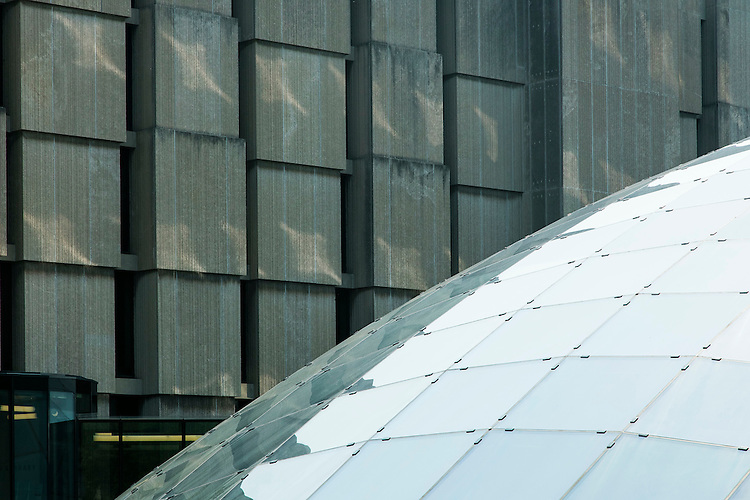 The glass and limestone facades of the Joe and Rika Mansueto Library (foreground) and Regenstein Library on the Hyde Park campus of the University of Chicago, summer 2015. (DePaul University/Jeff Carrion)