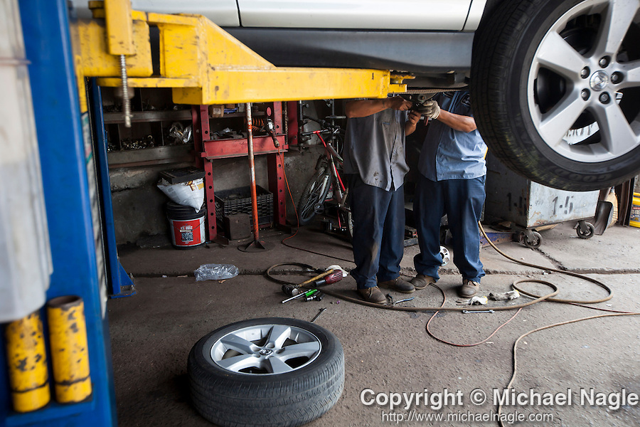 QUEENS, NY -- OCTOBER 22, 2013:  Mechanics work on a car in Willets Point on October 22, 2013 in Queens.  Photographer: Michael Nagle for The New York Times