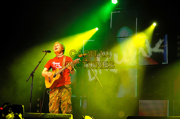 Ed Sheeran .performing at V Festival, Hylands Park, Chelmsford, Essex, England. .18th August 2012.on stage in concert live gig performance music half length red t-shirt tattoo singing green camouflage guitar.CAP/MAR.© Martin Harris/Capital Pictures.