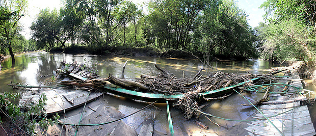 A 180 degree panoramic composite image of the decking and one arch of the destroyed McDowell Bridge partially submerged in the North Skunk River in the Millgrove Access Wildlife Area in southwest Poweshiek County, as seen on August 15, 2010.  The bridge, built in 1883 by King Iron Bridge Company, was one of 19 bowstring truss bridges remaining in Iowa before it was swept away by flood waters on the river over the weekend of August 14.