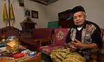 Mbah Maridjan with his favored Kansas cigarettes (two packs are a sure ticket to an interview) and his favored wayang character - Semar.