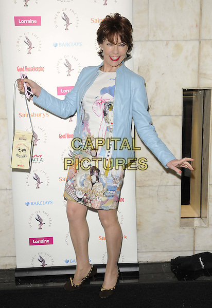 Kathy Lette .The Women Of The Year Lunch, Intercontinental hotel, Park Lane, London, England..October 17th, 2011.full length blue leather jacket white print dress bag hand arm posing side bag purse box.CAP/CAN.©Can Nguyen/Capital Pictures.