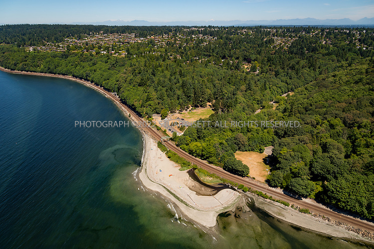 6/26/2015&mdash;Puget Sound, WA<br /> <br /> Carkeek Park<br /> <br /> Carkeek Park beach beyond the BNSF tracks. Esplanade NW in the distance<br /> Carkeek Park is a 216-acre (87.1 ha) park located in the Broadview neighborhood of Seattle, Washington. The park contains Piper Orchard, Pipers Creek (and its tributaries Venema Creek and Mohlendorph Creek), play and picnic areas, picnic shelters, and hiking trails. A pedestrian bridge across the main lines of the BNSF Railway connects to the Carkeek Park sand beach on Puget Sound. Park program activities are largely out of the Carkeek Park Environmental Learning Center.<br /> <br /> Photograph by Stuart Isett<br /> &copy;2015 Stuart Isett. All rights reserved.