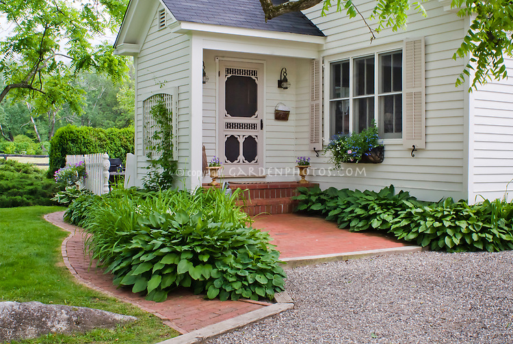 Curb appeal shaded front entrance porch of house with for Front porch landscaping plants