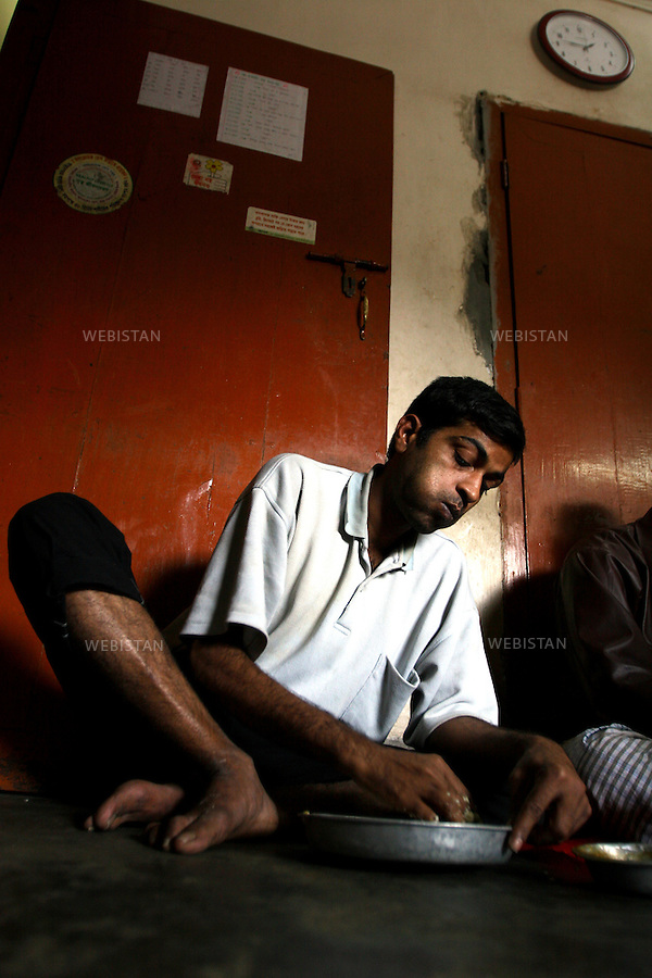 2006. Bangladesh, Dhaka. In the rehabilitation clinic, un patient has lunch..Patients at the clinic are responsible for preparing and serving meals. ..2006. Bangladesh, Dhaka. A la clinique de désintoxication, un patient déjeune..Des patients de la clinique sont en charge de la préparation et du service des repas. .