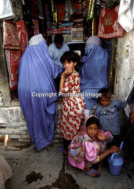 Unidentified women and children at a local market on July 23, 1996 in Herat, Afghanistan. The women are not alloved to study or work by the ruling Taliban regime. The women are forced to wear a traditional Burka dress that covers them from top to toe..Photo: Per-Anders Pettersson Kod: 4282