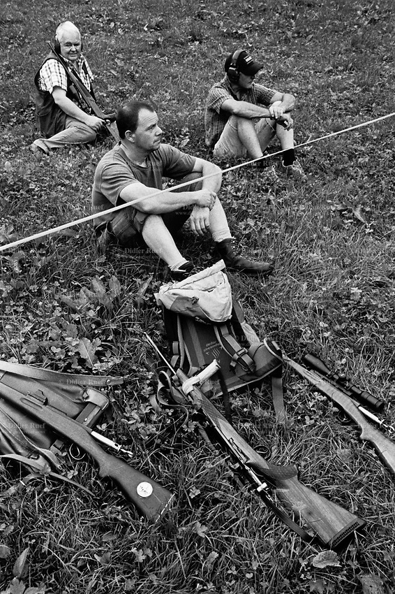 Switzerland. Canton Bern. Brienz. A group of men are seated on the grass and wait for their turn to shoot their rifles at Schiessstand (Shooting range) Engi during the 2016 Brienzer Jagdschiesssen (Hunter shooting competition days). 30.07.2016  © 2016 Didier Ruef
