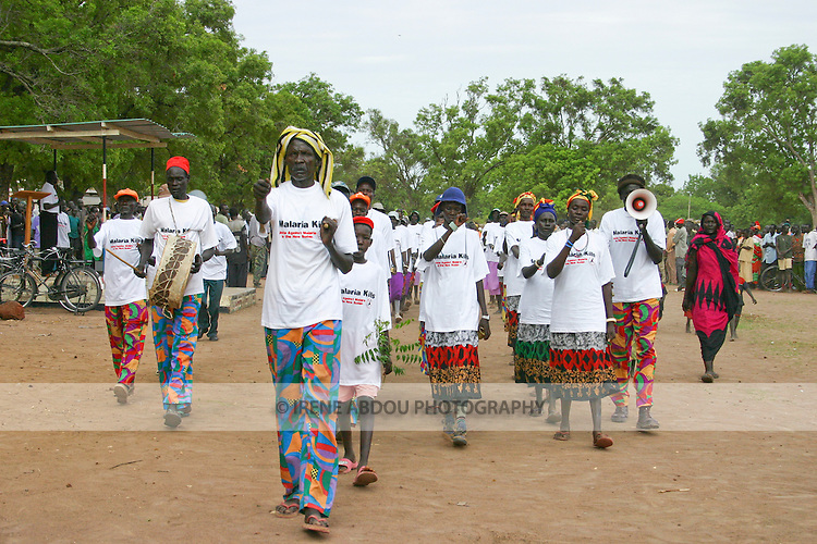 Organized by the international NGO, Population Services International (PSI), men and women from two Dinka folklore groups march into Rumbek's Freedom Square on AFrica Malaria Day.