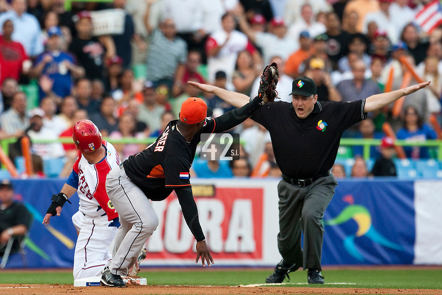 11 March 2009: #23 Jesus Feliciano of Puerto Rico slides safely at third as #2 Yurendell DeCaster of the Netherlands tags him in front of umpire Corrie Davis during the 2009 World Baseball Classic Pool D game 6 at Hiram Bithorn Stadium in San Juan, Puerto Rico. Puerto Rico wins 5-0 over the Netherlands