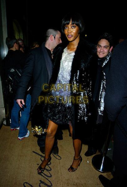 NAOMI CAMPBELL.At the Marc by Marc Jacobs a/w 2007/8 catwalk show,.Claridge's, London, England, February 16th 2007..full length black shiny coat jacket white grey dress fur collar.CAP/CAN.©Can Nguyen/Capital Pictures